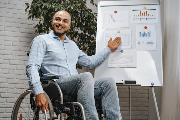 車椅子の若いアフリカ系アメリカ人の障害者の男性がホワイトボードのオフィスでプレゼンテーションを行います