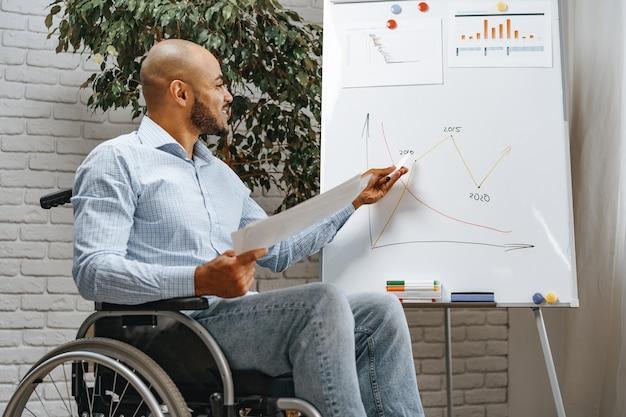 車椅子の若いアフリカ系アメリカ人の障害者の男性がホワイトボードでオフィスでプレゼンテーションを行います
