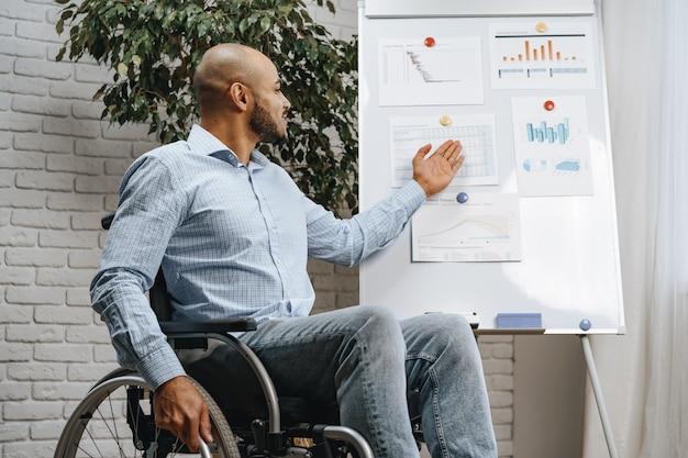휠체어를 탄 젊은 흑인 장애인이 사무실에서 화이트보드로 프레젠테이션을 한다