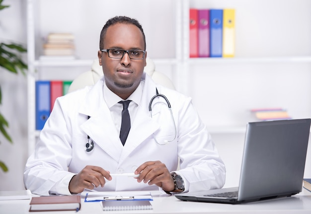 Young african american doctor is sitting in his office.