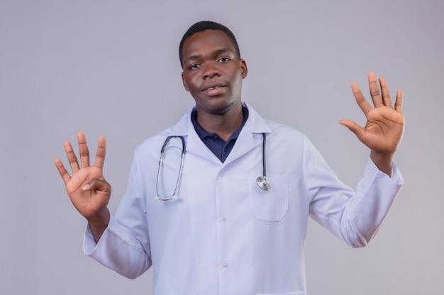 首に聴診器を備えた白衣を着た若いアフリカ系アメリカ人医師は、孤立した白い背景の上に彼の顔に笑顔で9本の指を上げます