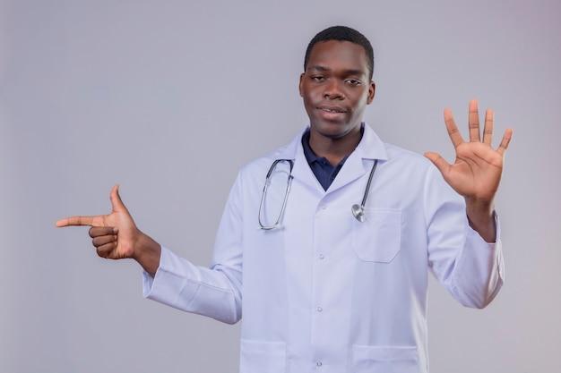 Giovane medico afroamericano che indossa camice bianco con lo stetoscopio che sembra fiducioso che mostra il numero cinque e che indica con il dito indice a lato