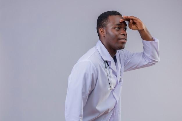 聴診器で白衣を着た若いアフリカ系アメリカ人医師が誰かを見るために頭を越えて遠くを見ています