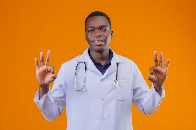 Young african american doctor wearing white coat with stethoscope relaxing doing meditation gesture with fingers smiling