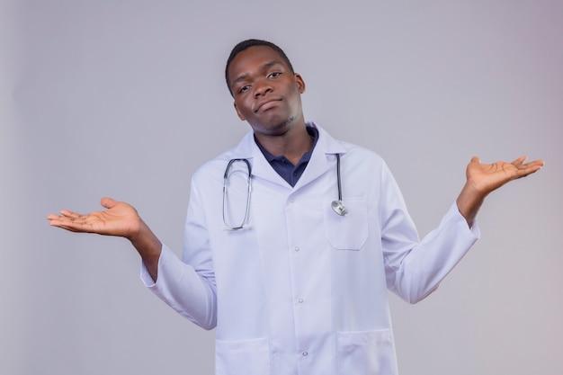 Giovane medico afroamericano che indossa camice bianco con lo stetoscopio che scrolla le spalle, guardando i palmi delle mani incerti e confusi