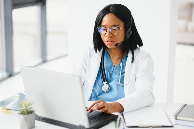 クリニックでラップトップに取り組んでいる若いアフリカ系アメリカ人の医師