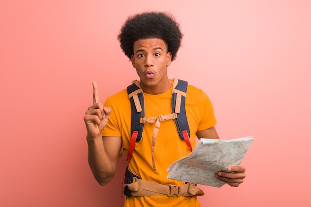 Young african american explorer man holding a map having a great idea, concept of creativity