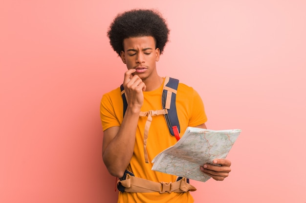 Young african american explorer man holding a map relaxed thinking about something looking at a copy space