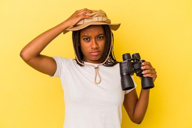 ショックを受けている黄色の背景に分離された双眼鏡を持っている若いアフリカ系アメリカ人の探検家の女性、彼女は重要な会議を覚えています。
