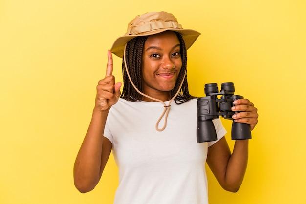 指でナンバーワンを示す黄色の背景に分離された双眼鏡を保持している若いアフリカ系アメリカ人の探検家の女性。
