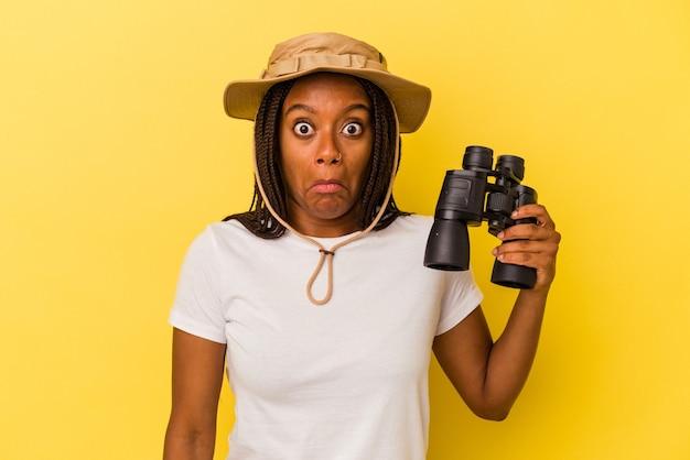 黄色の背景に分離された双眼鏡を持っている若いアフリカ系アメリカ人の探検家の女性は、肩をすくめると混乱した目を開いています。