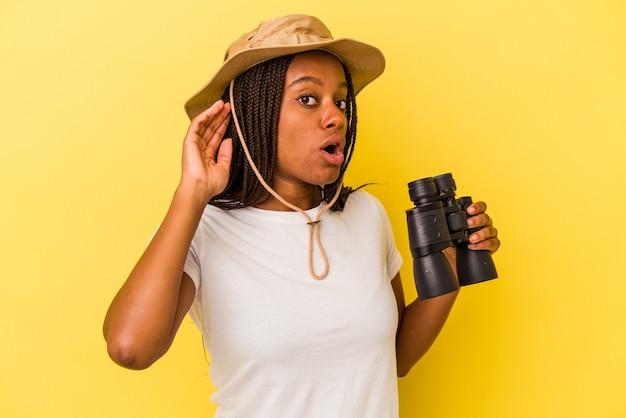 ゴシップを聴こうとしている黄色の背景に分離された双眼鏡を保持している若いアフリカ系アメリカ人の探検家の女性。