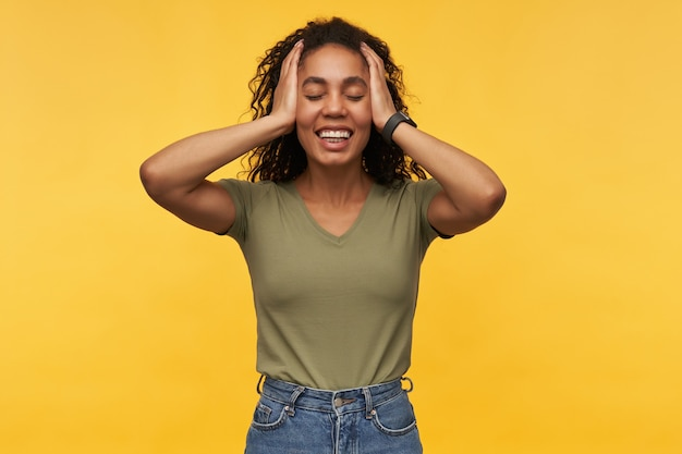 若いアフリカ系アメリカ人の女性は、腕で口を閉じ、目を大きく開いたままにする