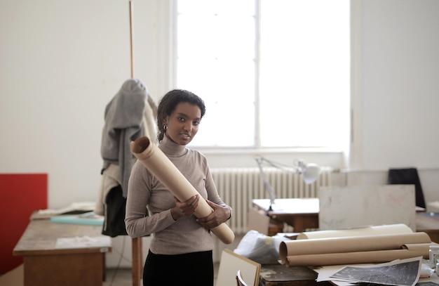 Молодая афро-американская женщина, держащая рулон бумаги дома