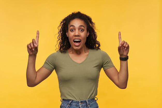 젊은 아프리카 계 미국인 여성은 녹색 티셔츠를 입고 데님 바지는 양손으로 위쪽을 나타냅니다.