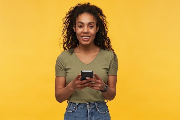 젊은 아프리카 계 미국인 여성, 녹색 티셔츠와 데님 바지를 입고 전화로 메시지를 입력하고 카메라를 응시하고 넓게 미소를 짓습니다.