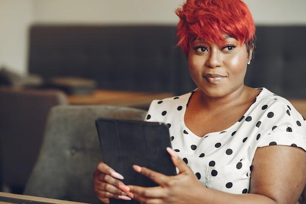 オフィスで働く若いアフリカ系アメリカ人の女性。白いブラウスの女性。