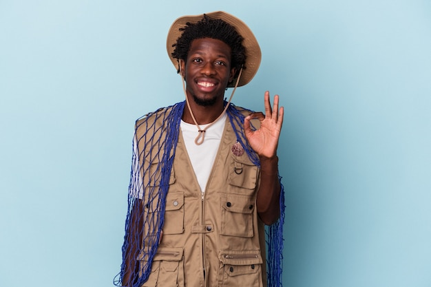 Young african american fisherman holding a net isolated on blue background cheerful and confident showing ok gesture.