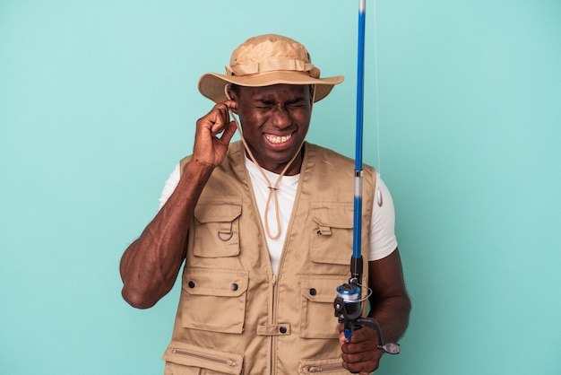 Young african american fisherman holding rod isolated on blue background covering ears with hands.