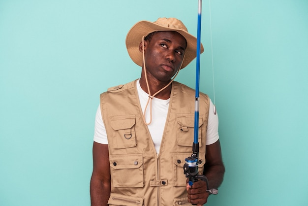Young african american fisherman holding rod isolated on blue background dreaming of achieving goals and purposes
