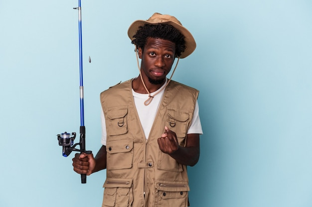 Young african american fisherman holding a rod isolated on blue background pointing with finger at you as if inviting come closer.