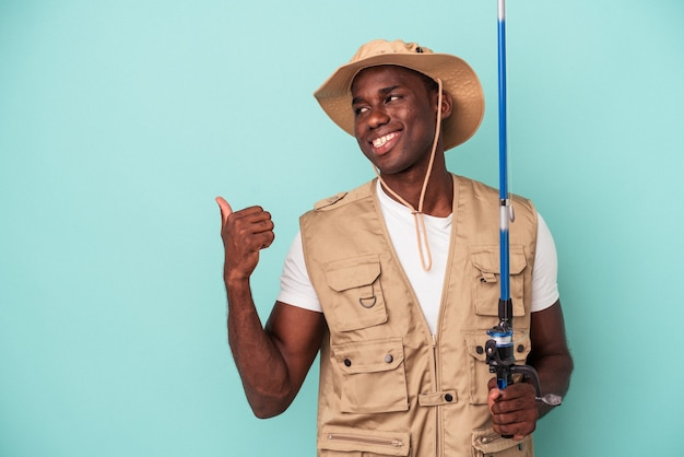 Young african american fisherman holding rod isolated on blue background points with thumb finger away, laughing and carefree.