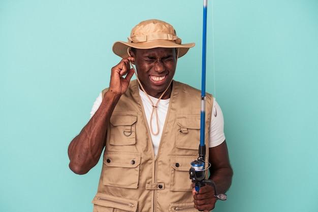 手で耳を覆う青い背景に分離されたロッドを保持している若いアフリカ系アメリカ人の漁師。