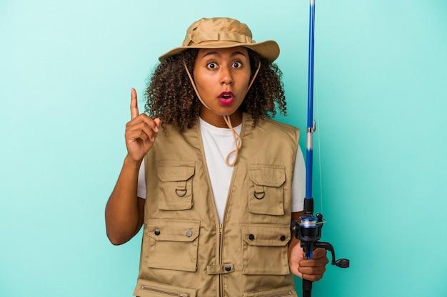 Молодая афро-американская рыбачка, держащая штангу, изолированную на синем фоне, имея идею, концепцию вдохновения.