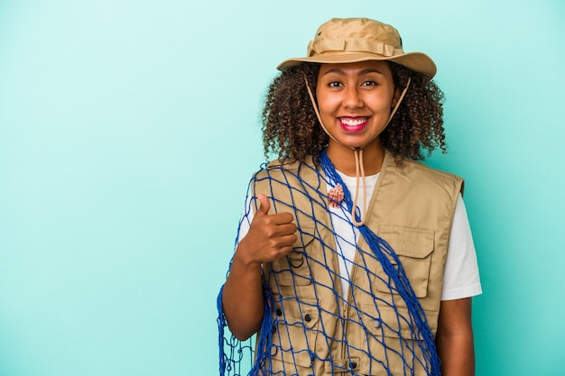 Young african american fisherwoman holding net isolated on blue background  smiling and raising thumb up