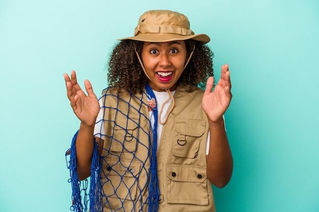 Молодая афро-американская рыбачка, держащая сеть изолирована на синем фоне, получая приятный сюрприз, возбужденная и поднимающая руки.
