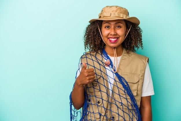 Молодая афро-американская рыбачка, держащая сеть изолирована на синем фоне, улыбается и поднимает палец вверх