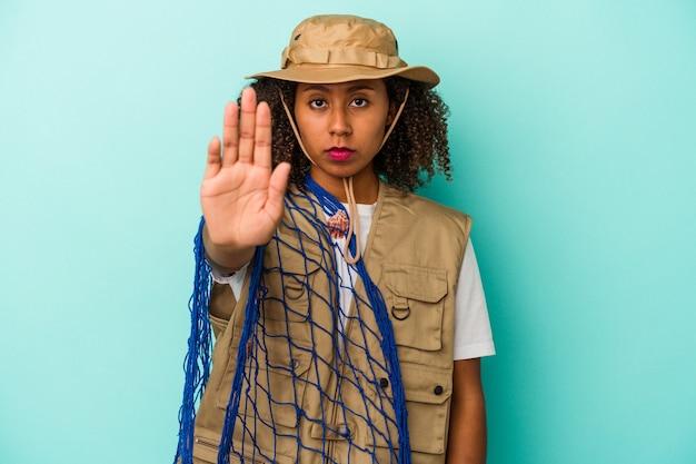 Молодая афро-американская рыбачка, держащая сеть, изолированная на синем фоне, стоя с протянутой рукой, показывая знак остановки, предотвращая вас.