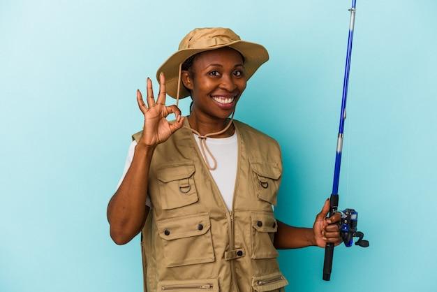 파란색 배경에 격리된 막대를 들고 있는 젊은 아프리카계 미국인 어부는 명랑하고 자신감 있는 확인 제스처를 보여줍니다.