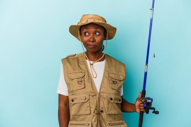 파란색 배경에 격리된 막대를 들고 있는 젊은 아프리카계 미국인 어부는 혼란스럽고 의심스럽고 확신이 서지 않습니다.