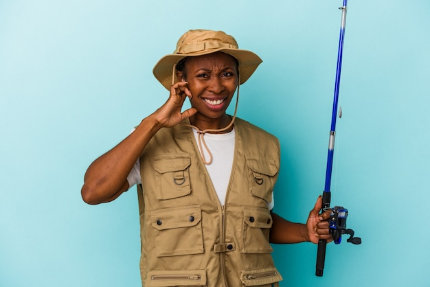손으로 귀를 덮고 파란색 배경에 고립 된 막대를 들고 젊은 아프리카계 미국인 어부.