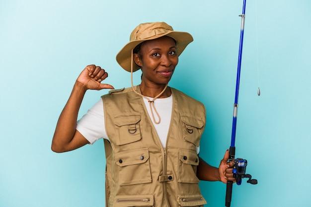 파란색 배경에 격리된 막대를 들고 있는 젊은 아프리카계 미국인 어부는 자랑스럽고 자신감이 넘치는 예를 보여줍니다.