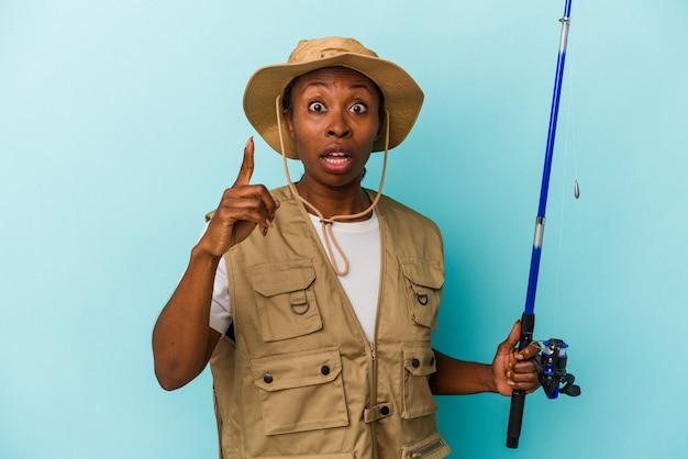 아이디어, 영감 개념을 가진 파란색 배경에 고립 된 막대를 들고 젊은 아프리카 계 미국인 어부.