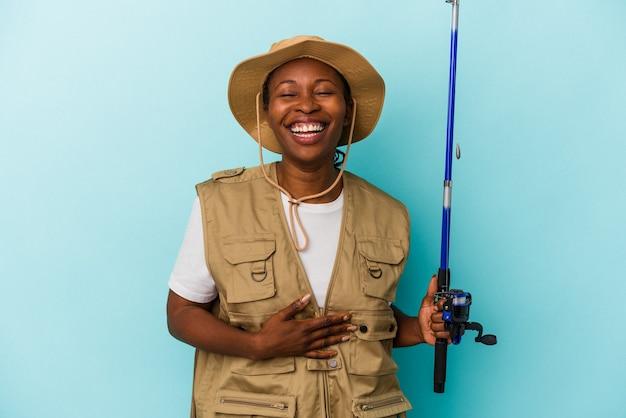 파란색 배경에 격리된 막대를 들고 웃고 있는 젊은 아프리카계 미국인 어부.