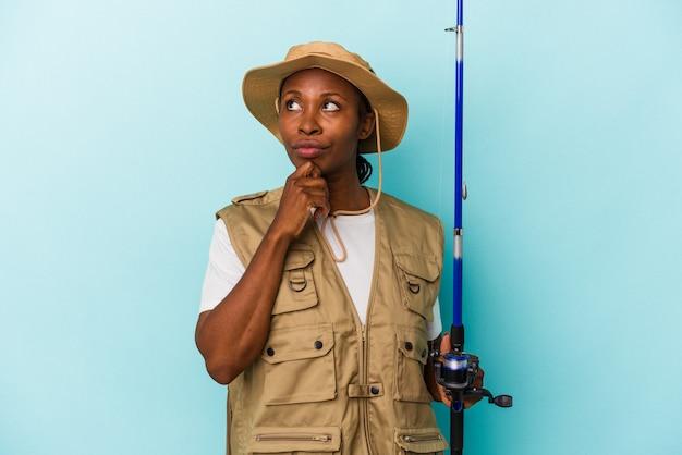 파란색 배경에 격리된 막대를 들고 있는 젊은 아프리카계 미국인 어부는 의심스럽고 회의적인 표정으로 옆을 바라보고 있습니다.