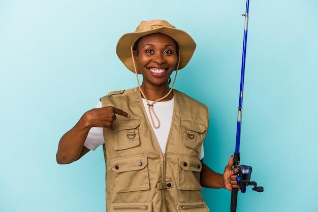 파란색 배경에 격리된 막대를 들고 있는 젊은 아프리카계 미국인 어부, 자랑스럽고 자신감 있는 셔츠 복사 공간을 손으로 가리키는 사람