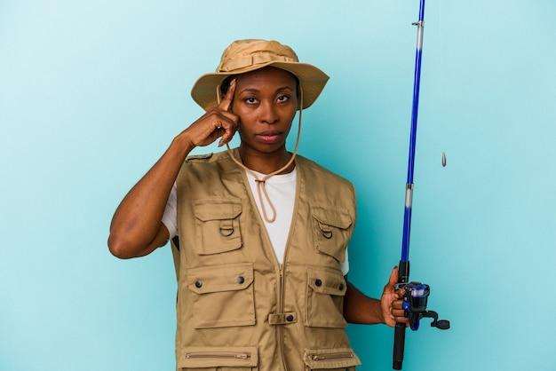 파란색 배경에 격리된 막대를 들고 있는 젊은 아프리카계 미국인 어부는 손가락으로 사원을 가리키며 생각하고 작업에 집중했습니다.