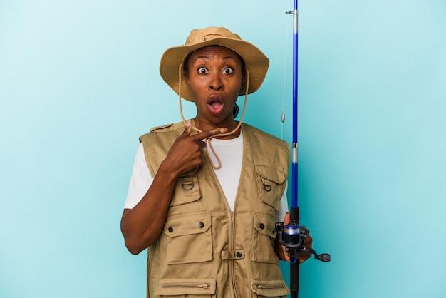 측면을 가리키는 파란색 배경에 고립 된 막대를 들고 젊은 아프리카 계 미국인 어부