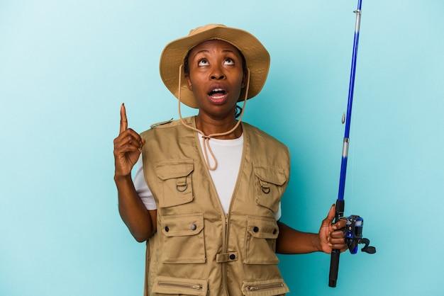 열린 입으로 거꾸로 가리키는 파란색 배경에 고립 된 막대를 들고 젊은 아프리카 계 미국인 어부.