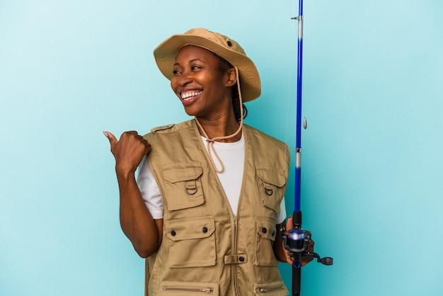 파란색 배경에 격리된 막대를 들고 있는 젊은 아프리카계 미국인 어부는 엄지손가락을 치켜들고 웃고 평온합니다.