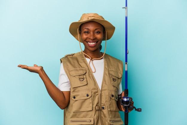 파란색 배경에 격리된 막대를 들고 손바닥에 복사 공간을 보여주고 허리에 다른 손을 잡고 있는 젊은 아프리카계 미국인 어부.