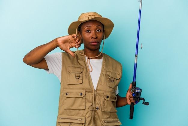파란색 배경에 격리된 막대를 들고 있는 젊은 아프리카계 미국인 어부는 싫어한다는 제스처를 보이고 엄지손가락을 아래로 내립니다. 불일치 개념입니다.