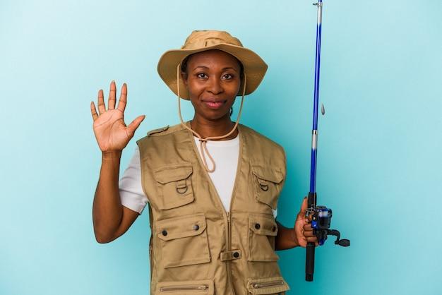 파란색 배경에 격리된 막대를 들고 있는 젊은 아프리카계 미국인 어부는 손가락으로 5번을 보여주며 쾌활하게 웃고 있습니다.