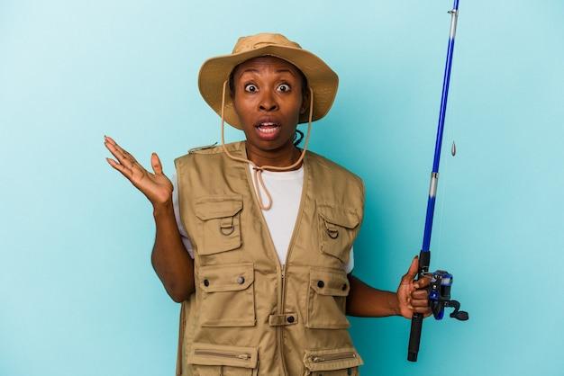 파란색 배경에 격리된 막대를 들고 있는 젊은 아프리카계 미국인 어부는 놀라고 충격을 받았습니다.