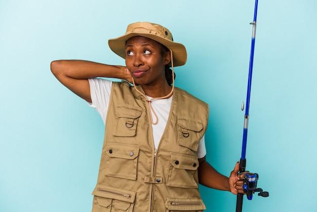 파란색 배경에 격리된 막대를 들고 머리 뒤쪽을 만지고 생각하고 선택하는 젊은 아프리카계 미국인 어부.