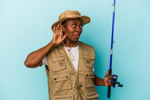 파란색 배경에 격리된 막대를 들고 가십을 들으려고 하는 젊은 아프리카계 미국인 어부.